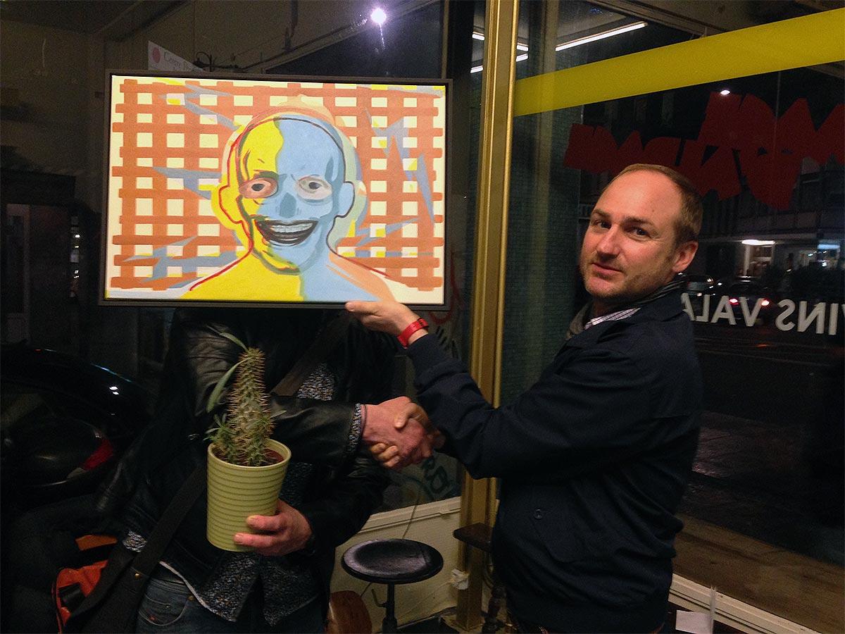 """T.B. avec le tableau """"Face (A)"""" félicité par un des membres du jury."""